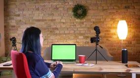 Opinião traseira do close up o blogger fêmea atrativo novo para viver a fluência no portátil com a tela verde dentro no apartamen filme