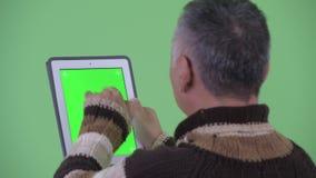 Opinião traseira do close up o homem japonês maduro feliz que usa a tabuleta digital video estoque