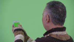 Opinião traseira do close up o homem japonês maduro feliz que usa o telefone vídeos de arquivo