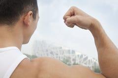 Opinião traseira do close-up o homem novo que dobra seu bíceps, fora no Pequim, inclinação da câmera Imagens de Stock Royalty Free