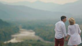 Opinião traseira do close-up do zangão nos pares de beijo alegres no fundo da paisagem bonita do rio filme