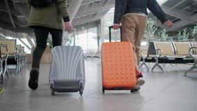 Opinião traseira dois povos de passeio com a mala de viagem do rolamento no salão do aeroporto filme
