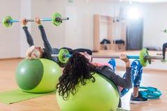 Opinião traseira duas mulheres que levantam o barbell que encontra-se na bola da estabilidade ao exercitar no gym imagens de stock