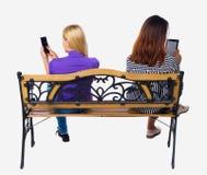 Opinião traseira duas mulheres que sentam-se no banco e nos olhares na tela a tabuleta Imagem de Stock