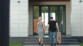 Opinião traseira entrando do hotel dos pares do viajante Casa de vinda dos pares modernos com saco vídeos de arquivo