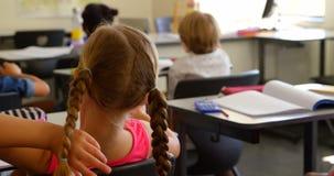 Opini?o traseira a estudante caucasiano que senta-se na mesa em uma sala de aula na escola 4k filme