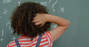 Opinião traseira a estudante da misturado-raça que risca sua cabeça na sala de aula na escola 4k filme