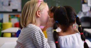 Opinião traseira a estudante da misturado-raça que sussurra em sua orelha dos colegas na sala de aula 4k filme