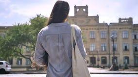 A opinião traseira a estudante universitário com cabelo longo que anda em cima à universidade, apronta-se para estudar video estoque