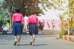 Opini?o traseira estudantes preliminares da felicidade na camisa cor-de-rosa e na caminhada azul da saia ?s salas de aula imagem de stock