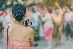 A opinião traseira a fêmea no vestido tailandês toma uma foto de uma parada tailandesa da dança no festival de Songkran imagens de stock royalty free