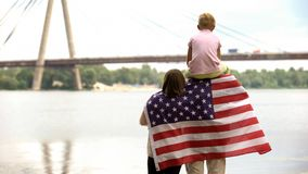 Opinião traseira a família envolvida na bandeira dos EUA que olha a ponte, Dia da Independência imagens de stock royalty free