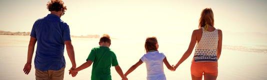 Opinião traseira a família que guarda as mãos ao andar junto na costa fotos de stock