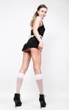 Opinião traseira a jovem mulher bonita vestida como um empregada-empregado 'sexy' em um uniforme skimpy, levantando provocatively Foto de Stock Royalty Free