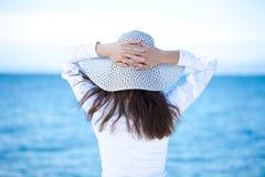 Opinião traseira a jovem mulher, estando na praia Imagem de Stock