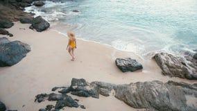 Opinião traseira a jovem mulher no roupa de banho amarelo que anda afastado na praia branca tropical bonita da areia vídeos de arquivo