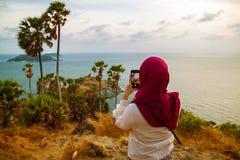 Opinião traseira a jovem mulher que fotografa a paisagem da montanha pela câmera do smartphone no por do sol sobre o mar foto de stock royalty free