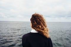 Opinião traseira a jovem mulher que olha o céu nublado e o mar cinzento imagem de stock royalty free