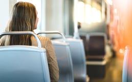 Opinião traseira a jovem mulher que senta em público o transporte imagens de stock