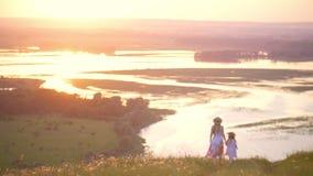A opinião traseira a mãe e a filha pequena que guardam as mãos anda abaixo do monte com vista perfeita no rio no por do sol filme