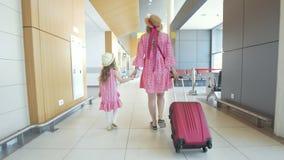 Opinião traseira a mãe e a filha pequena que guardam as mãos que andam à sala de espera no aeroporto filme