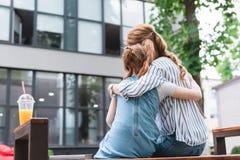 opinião traseira a mãe e a filha que abraçam-se ao descansar no banco foto de stock royalty free