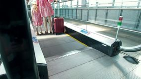 Opinião traseira a mamã e a filha pequena que vão abaixo da escada rolante no aeroporto filme