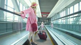 Opinião traseira a mamã e a filha pequena que vão abaixo da escada rolante no aeroporto video estoque
