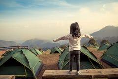A opinião traseira a menina asiática expande seus braços no acampamento fotos de stock
