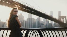 Opinião traseira a menina bonita com o cabelo do voo que inclina-se na cerca da terraplenagem do rio na ponte de Brooklyn, olhand video estoque