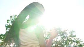 A opinião traseira a menina bonita nova com teme dançar em um parque Mulher bonita nos óculos de sol que escuta a música e vídeos de arquivo