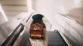 Opinião traseira a menina bonito pequena que move-se em cima na escada rolante Roupa da criança o estilo francês que vai à escola vídeos de arquivo