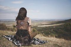 Opinião traseira a menina de Boho em um monte que olha distante na distância Imagem de Stock