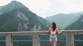 Opinião traseira a menina do turista que está na ponte Djurdjevic em Montenegro, estilo de vida do curso vídeos de arquivo