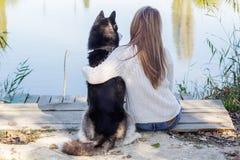 A opinião traseira a menina está abraçando o cão ronco fora Fotografia de Stock Royalty Free