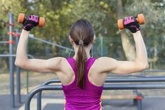 A opinião traseira a menina magro no treinamento brilhante do sportswear com pesos para os bíceps no sportground exterior Fones d foto de stock royalty free