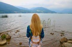 Opinião traseira a menina que está a água próxima e que olha o horizonte com montanhas Foto de Stock