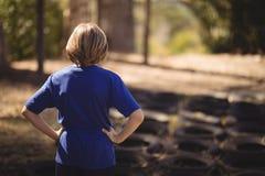 Opinião traseira a menina que está com mãos no quadril durante o curso de obstáculo foto de stock