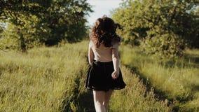 Opinião traseira a moça bonita que veste a saia preta com o cabelo ondulado corrido dentro em risos da floresta e sorrisos e rota vídeos de arquivo