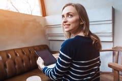 A opinião traseira a moça está fazendo a compra na loja em linha através da almofada de toque, quando sentar o café no dia de mol Foto de Stock