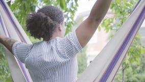 Opinião traseira a mulher afro-americano nova que senta-se na rede, relaxando no quintal, esticando seu corpo, aumentando vídeos de arquivo