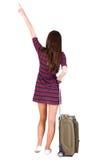 Opinião traseira a mulher apontando com a mala de viagem que olha acima Foto de Stock