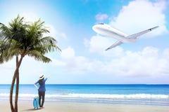 Opinião traseira a mulher asiática no chapéu com posição do saco da mala de viagem na praia imagens de stock royalty free