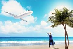 Opinião traseira a mulher asiática no chapéu com posição do saco da mala de viagem na praia fotografia de stock royalty free
