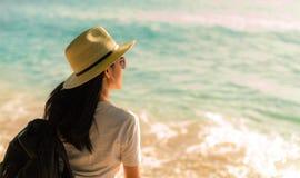 Opinião traseira a mulher asiática nova feliz na forma do estilo ocasional com chapéu de palha e trouxa Relaxe e aprecie o feriad imagens de stock