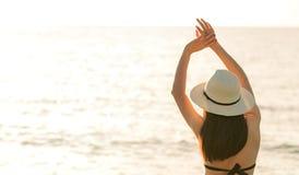 Opinião traseira a mulher asiática nova feliz no chapéu preto do biquini e de palha para relaxar e apreciar na praia tropical do  imagem de stock