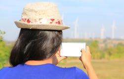 Opinião traseira a mulher asiática nova que toma a foto com o smartphone do campo da turbina eólica imagens de stock