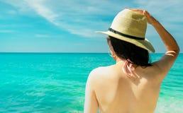 Opinião traseira a mulher asiática nova 'sexy' para vestir o biquini, o chapéu de palha, e os óculos de sol cor-de-rosa que relax fotografia de stock royalty free