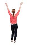 Opinião traseira a mulher bonita nas calças de brim que olham a parede e as posses Fotografia de Stock