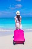 Opinião traseira a mulher bonita nova com a grande mala de viagem na praia tropical Imagem de Stock Royalty Free